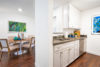 Kitchen sink with cabinets and grey counter top opens to dinning area.